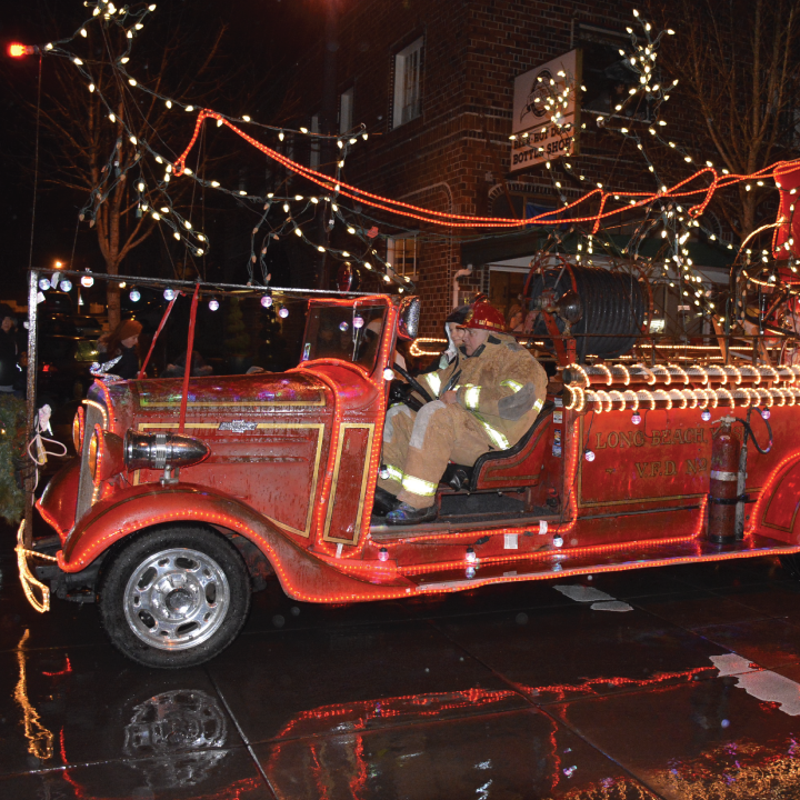 Vintage fire truck lit with Christmas lights at night