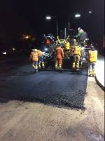 Street paver at night with workers