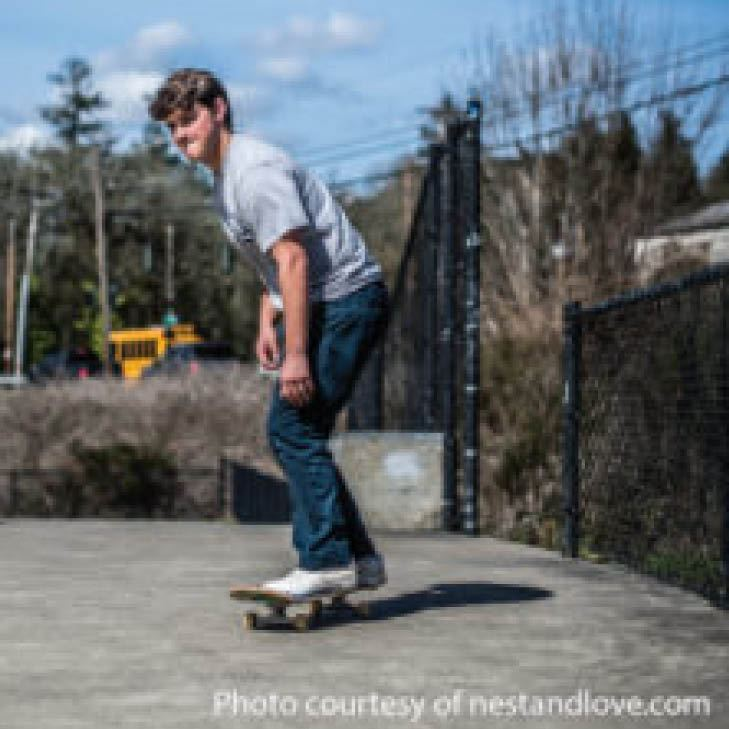 Teenager on skate board outdoors