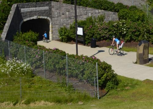 Adult and children bicycling toward a pedestrian tunnel